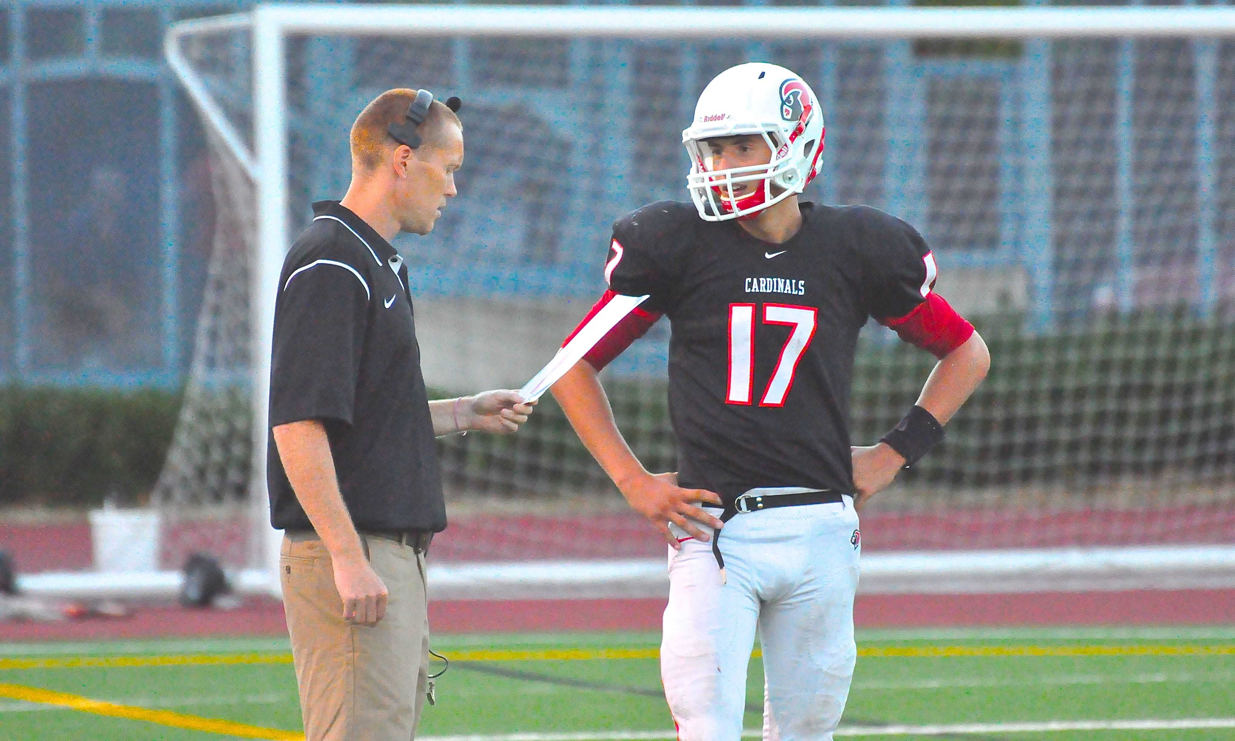Former head football coach Adam Grimes (left) talks with junior quarterback Nate Ostmo during the Cards' 41-26 loss to Wilson on Aug. 30.
