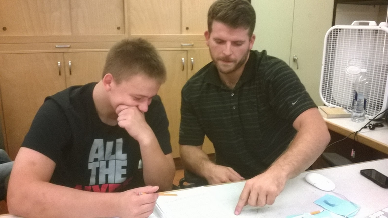 Alex Linnenkohl (right), helps junior Christian Needham with an assignment.