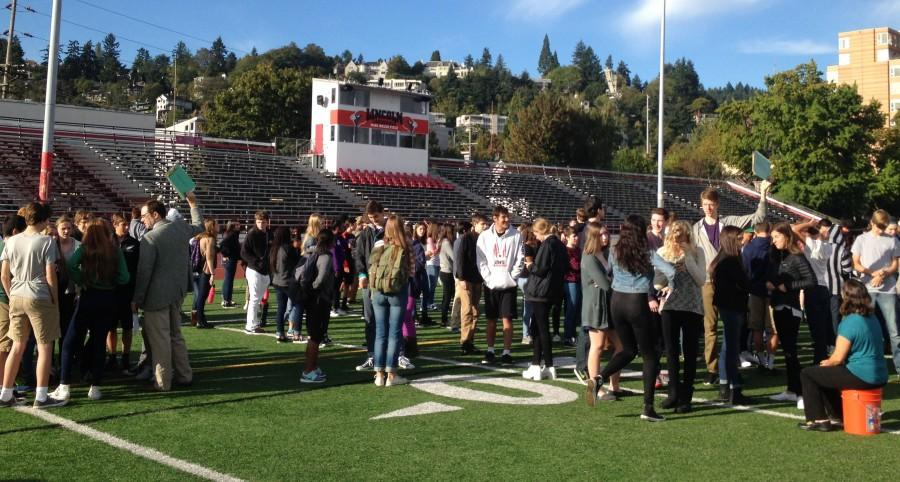 Students and staff gather on Mike Walsh Field in an earthquake preparedness safety drill Oct. 16.