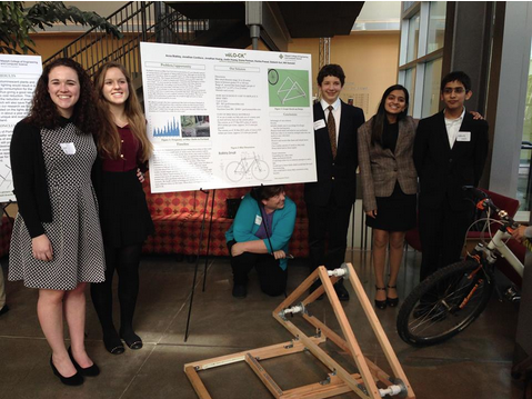 (from left) Juniors Anna Blakely, Emma Perlman, freshman Jonathan Cordisco, junior Ruhika Prasad, and sophomore Siddharth Suri stand in front of their presentation board and prototype while adviser Meg Kilmer crouches under the board.