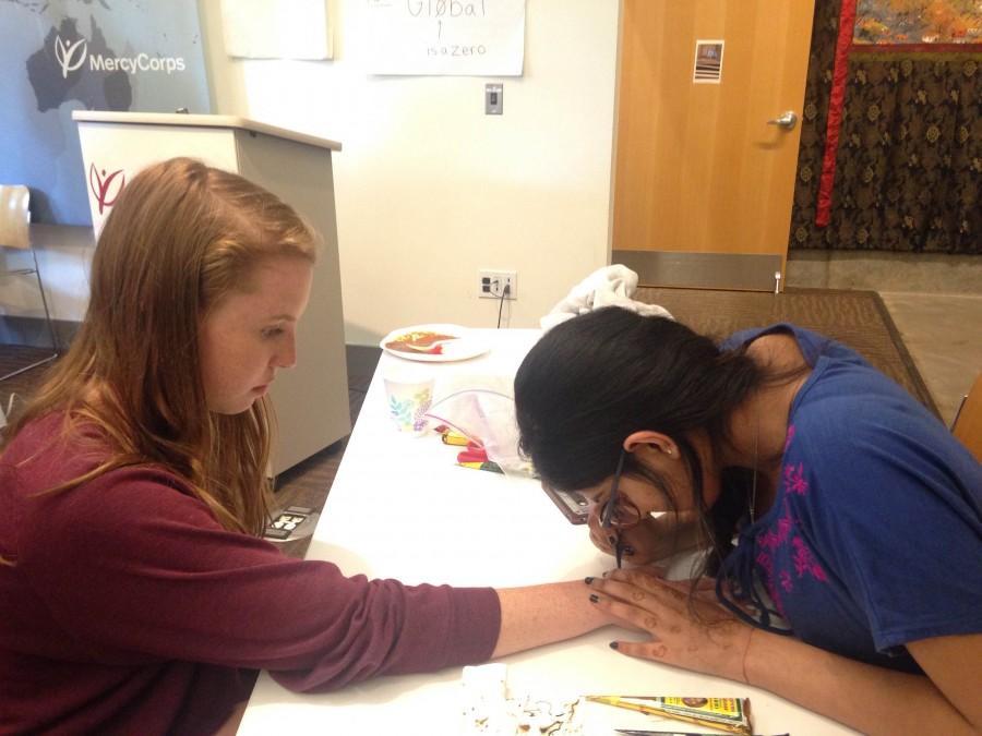 Junior Ruhika Prasad draws a henna design on a students hand.