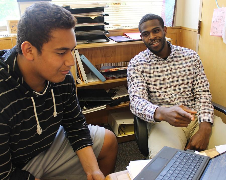 Ryan McCants (right) works with senior Tomasi Sanft in the attendance office.