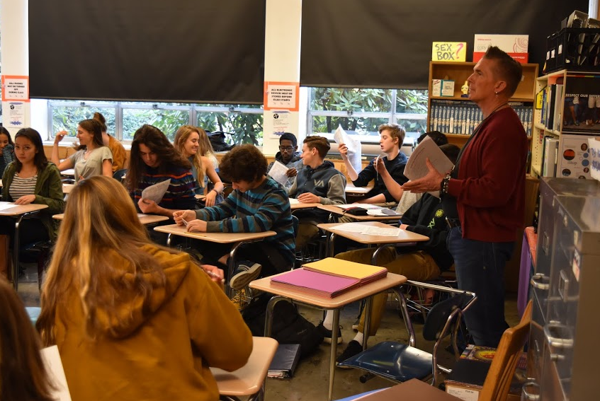 Teacher Timm Goldhammer passes out papers to his eight period health students.