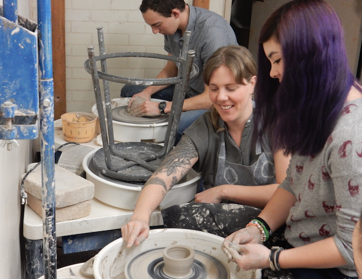 Abby Kessler assists student Bailey Smith on the pottery wheel.