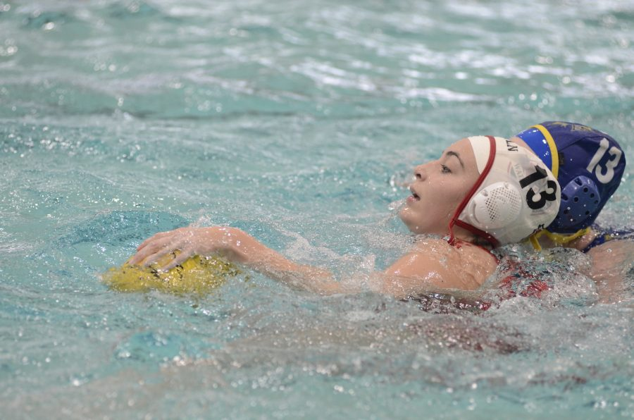 Senior Carli Tovar (white cap) faces a challenge from a Newberg player during the 3rd place match at the State Championships Nov. 12 in Corvallis. The Cardinals lost 7-6.