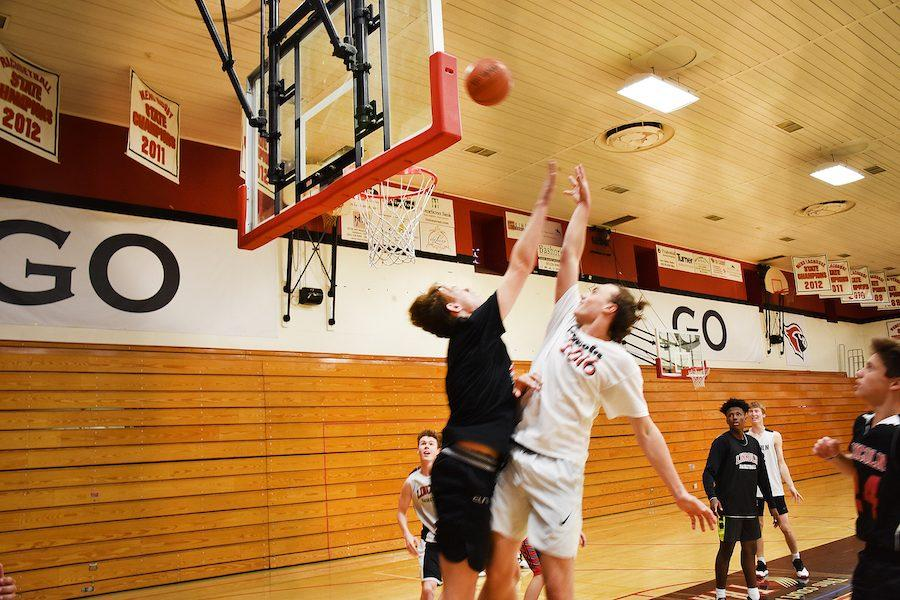 Junior Addy Phillips (black shirt) jumps to block a shot by junior Blake Phillips, as, from left to right, senior Joey Morones, junior Rasheed Butler and junior Isaac Baker look on.