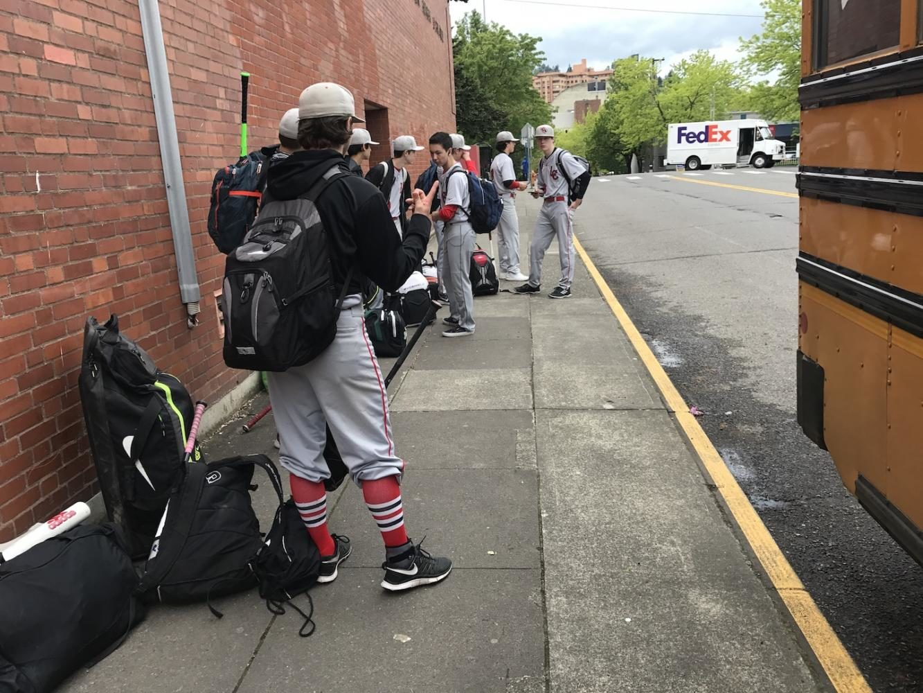 The+JV+baseball+team+waits+for+a+bus+outside+Lincoln+last+month.+Members+of+that+team+say+they+have+been+stuck+for+hours+waiting+on+buses+to+pick+them+up+after+games.
