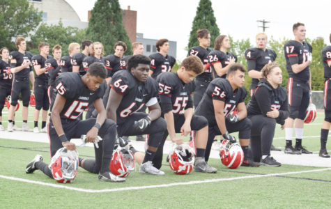 Lincoln football players kneel during the national anthem before a game against Madison on Sept. 22.
