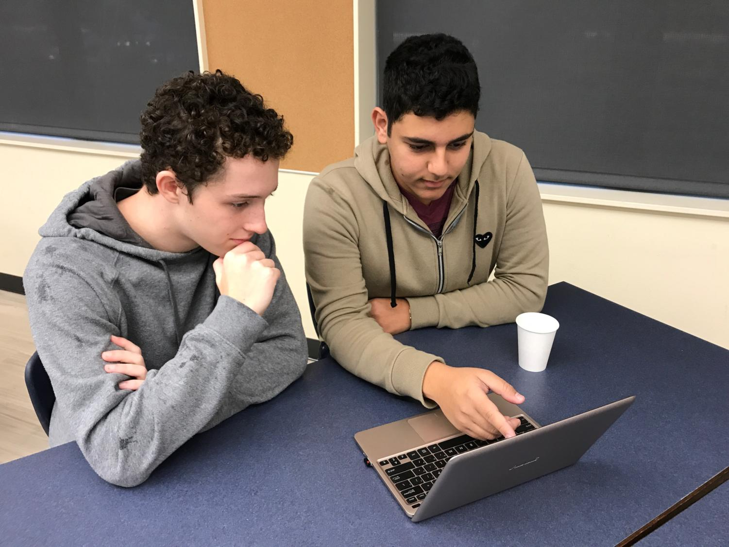 "Seniors Jacob Werbner (left) and Amahn Enayati discuss a lesson plan for ""Teen Tech Help,"" the program they run to teach senior citizens how to use technology."