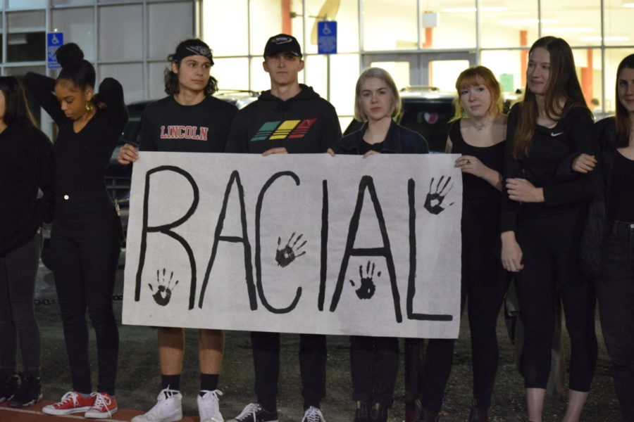 "Students held up three signs saying ""RACIAL,"" ""JUSTICE"" and ""NOW."" The protest on Oct. 27 featured 65 students."