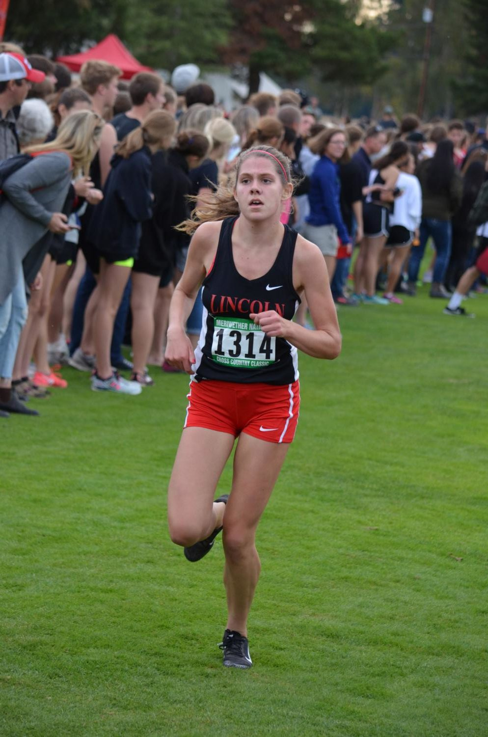 Ellie Kobak runs cross-country at the Meriwether Classic on Sept. 22. Kobak has overcome her own hearing loss to help others, recently winning a national award for her efforts.