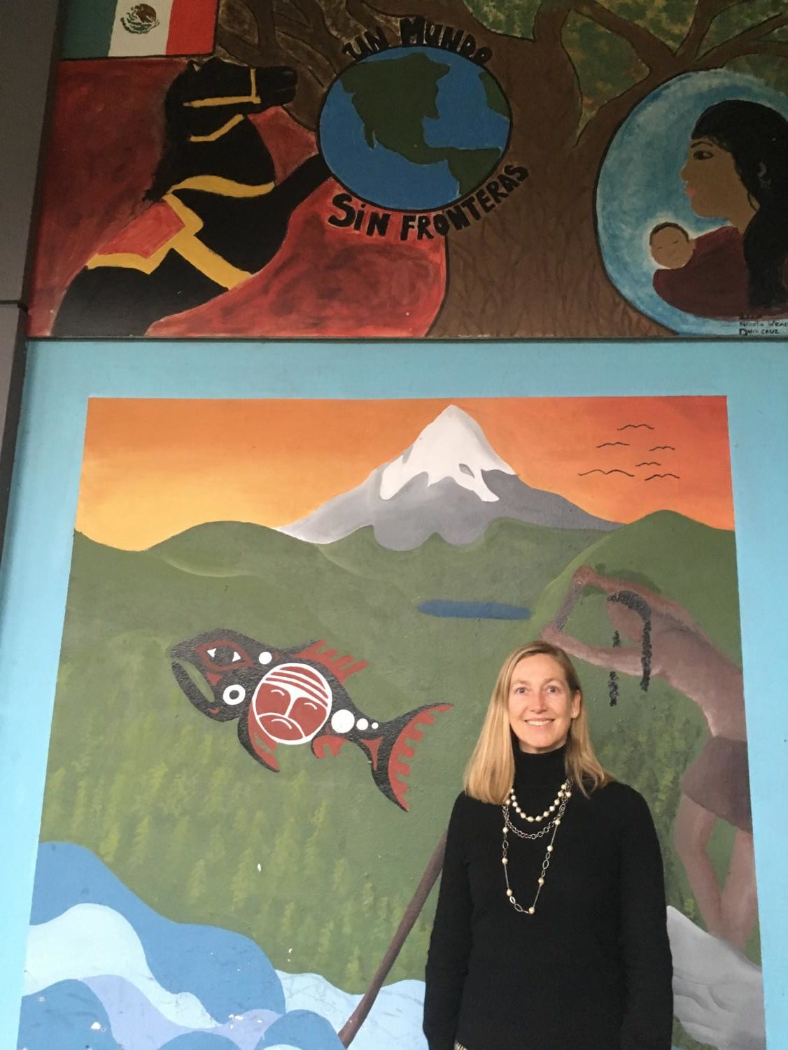 Principal Peyton Chapman stands in front of a mural that illustrates Lincoln's committment to a global education. Chapman would like this commitment to extend to the rest of the building in the rebuilt Lincoln.