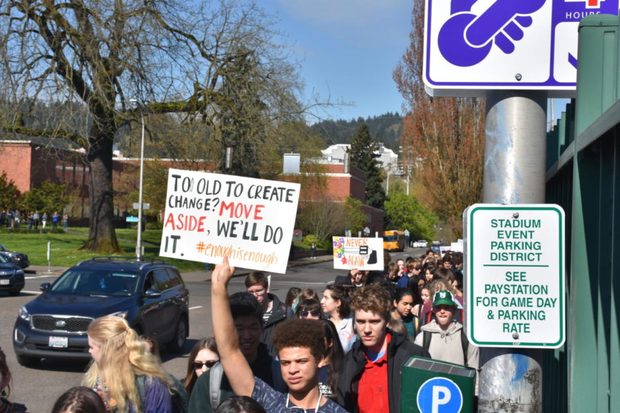 Junior Caleb Kono holds a sign as he and other Lincoln students walk out of class on April 20, protesting for gun reform and student safety. The students marched to City Hall, and 20 students rode a bus to Salem to speak in front of Oregon legislators.