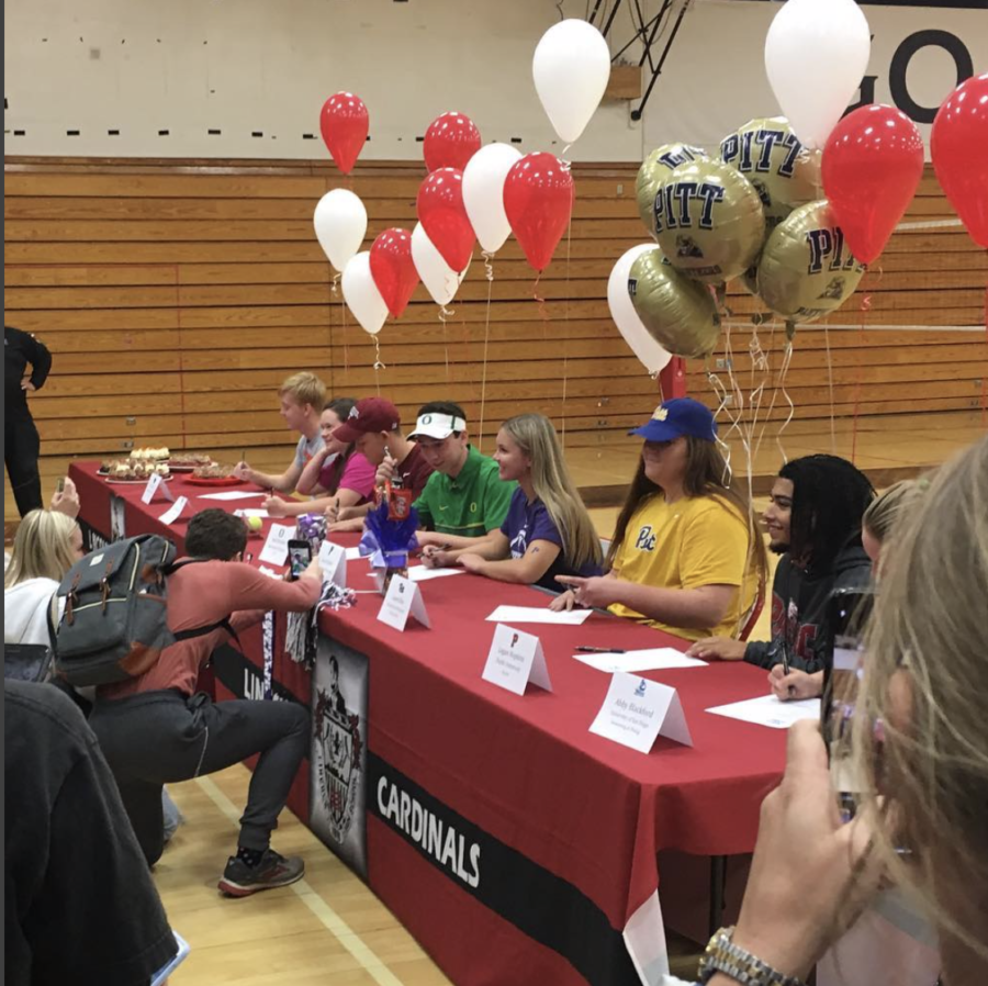 Friends%2C+family+and+coaches+gathered+in+the+gym+Nov.+14+during+lunch+to+honor+and+celebrate+senior+student+athletes%2C+as+they+signed+their+commitment+to+play+in+college.+