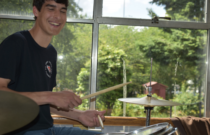 Senior Joe Thurston smiles as he rythymically hits a drumset. Thurston is an Eagle Scout, as well as a member of the Lincoln Percussion Ensemble who recently helped renovate the band room.
