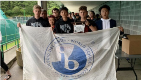 Lincoln Varsity Tennis team poses with an International Baccalaureate flag and their second place OSAA trophy upsidedown expressing their anger and disappointment with the organization.