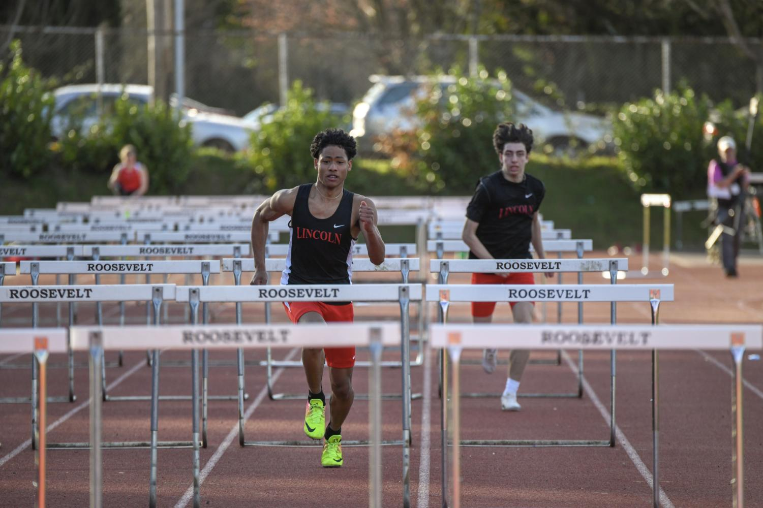 Freshman Justius Lowe leads the charge against junior Joey Abrams in a 110-meter high-hurdles race at Roosevelt on Mar 20.