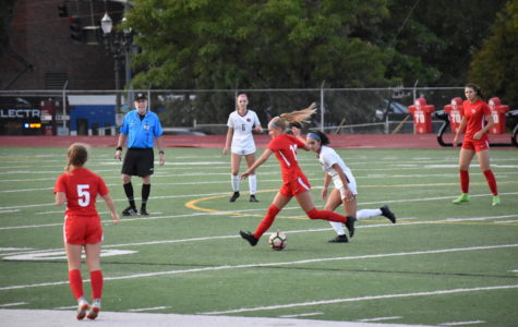 Junior Jolie Maycumber keeps the ball away from a defender during a varsity girls' soccer home game against Glencoe on Sept 12. Lincoln won 9-0. Along with girls soccer, other fall sports are underway, and coaches and players are excited for the season to come.