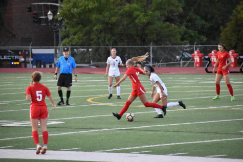 Junior Jolie Maycumber keeps the ball away from a defender during a varsity girls