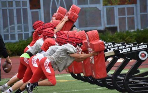 The JV football team prepares to tackle a seven-man sled. Lincoln's football practices correct tackling and wears Guardian helmet covers for concussion prevention.