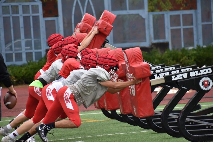 The+JV+football+team+prepares+to+tackle+a+seven-man+sled.+Lincoln%27s+football+practices+correct+tackling+and+wears+Guardian+helmet+covers+for+concussion+prevention.+