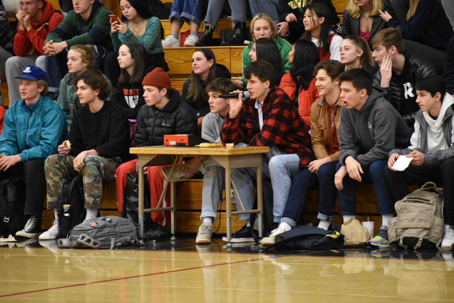 Senior Jake Berry MCs a Hoopfest game while a crowd watches from the bleachers. On Dec. 16, the Redeem Team and No Name team got into a fight, making spectators question whether stricter regulations should be set at Hoopfest.