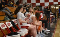 Freshman Morgan Miller, right, chats on the bench with her teammates during a varsity basketball game.