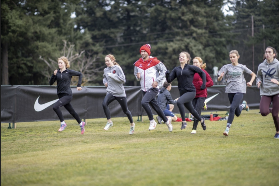 Eric Dettman, head cross country and track and field coach, strides with the girls cross country team before Nike Cross Nationals 2019.