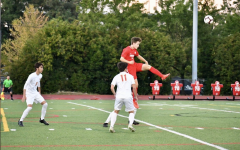 Senior Aidan McCabe leaps up above an opponent in a varsity soccer game at Lincoln last fall.