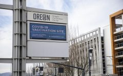 A sign outside the Oregon Convention Center designates it as a COVID vaccination site.