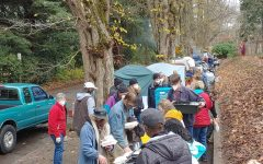 Houseless Portlanders line up to receive food outside Laurelhurst Park in SE Portland. Many have criticized the city of Portland for removing camps without a better option available to those who are being displaced.