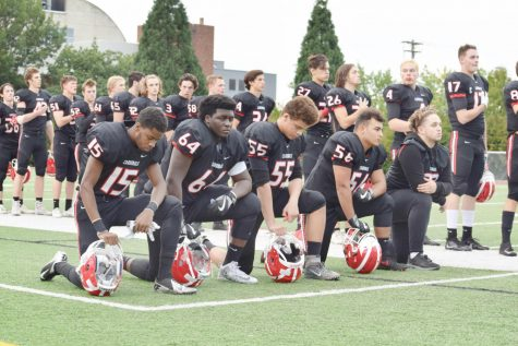 Lincoln football players kneel during the national anthem on Mike Walsh Field before a game against Madison, Sept. 22, 2017.