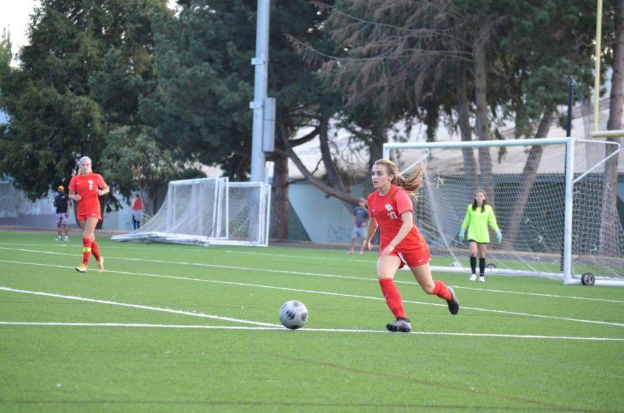 Junior Leeza Burke dribbles the ball as Senior Greta Halvorson onlooks. The Lincoln girl's soccer team is 4-3-1 this year.
